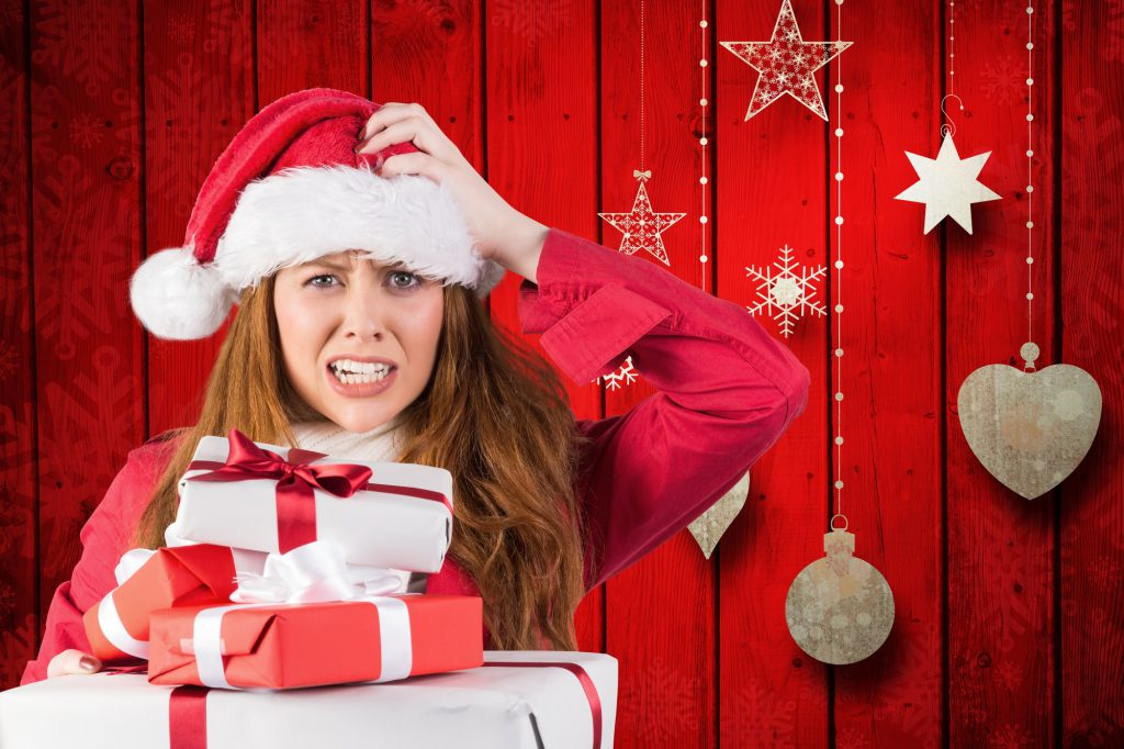 Confused woman in santa costume with a stack of christmas gifts